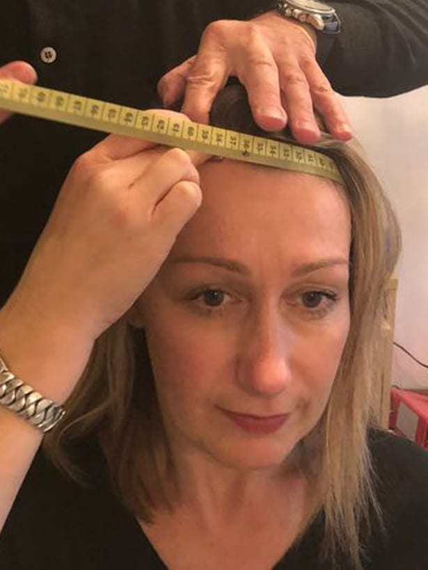 mujer midiendo la circunferencia de su cabeza para elegir el tamaño adecuado de peluca oncológica