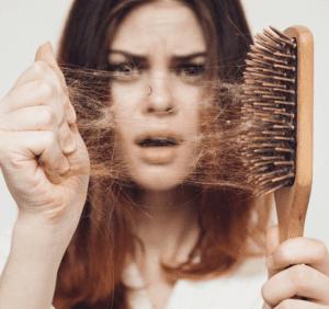 mujer quitando cabellos que han quedado en un cepillo del pelo.