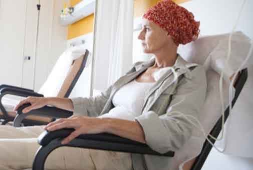 mujer recibiendo quimioterapia. Lleva un turbante oncológico debido a la caída del cabello asociada.